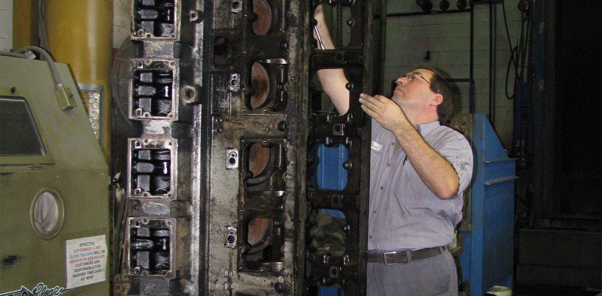 Un técnico de Maquinas Rutt, Inc. que limpia un motor desarmado